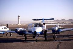 A man cleaning the window of a white and blue, twin engine airplane on the tarmac. The Dear Valley Airport tower is prominently featured in the background.