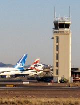 Good Year Airport tower with three large, white jets parked on the tarmac to its left.