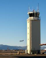 In the foreground, the Good Year Airport tower is prominently featured. In the background, there are two large, white jets parked on the tarmac and a white, single engine plane that is descending for a landing.
