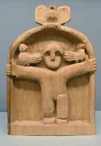 wood sculpture with a figure with outstretched arms and birds