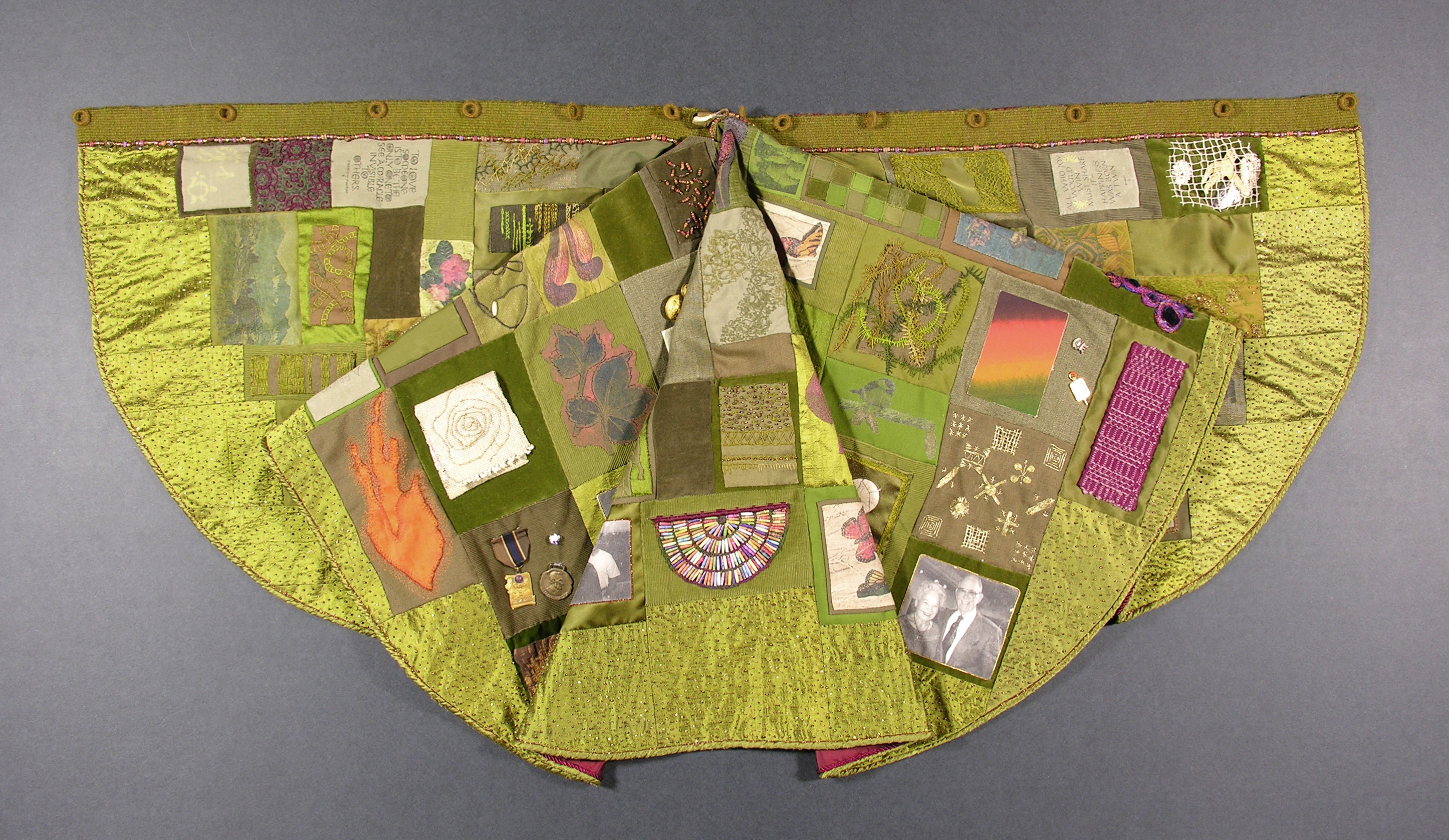 green art cape embellished with images and trinkets